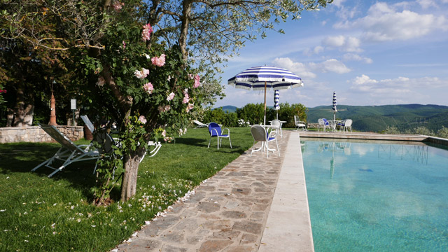 Infinity pool with sun umbrellas at Villa le Barone Tuscany